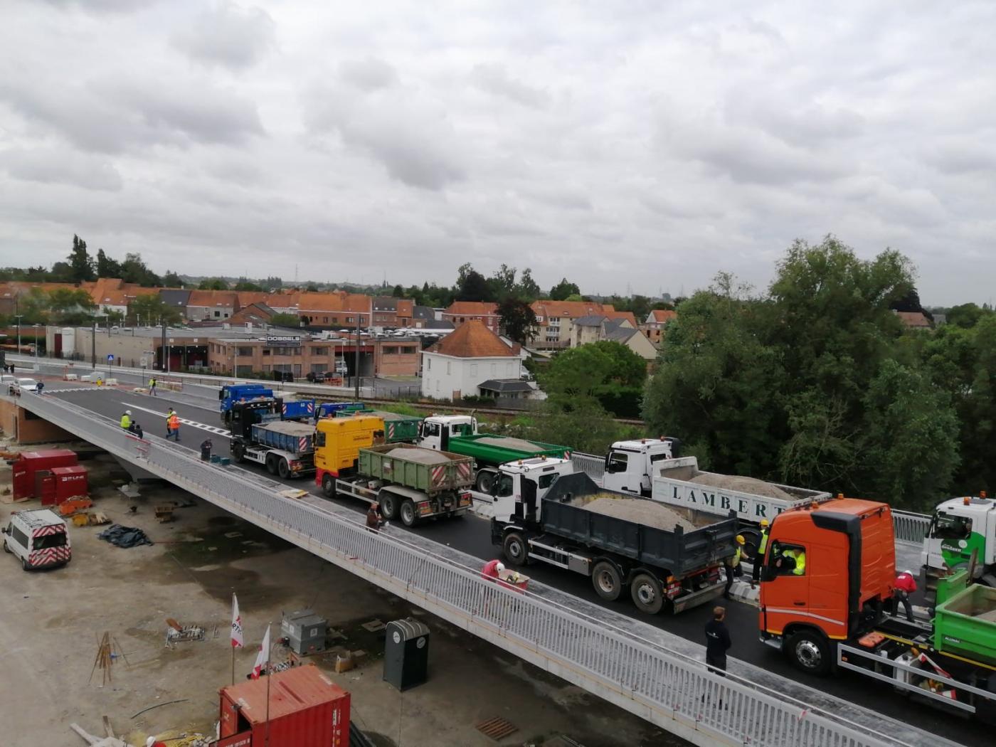 Volgeladen vrachtwagens testen de stevigheid van de brug
